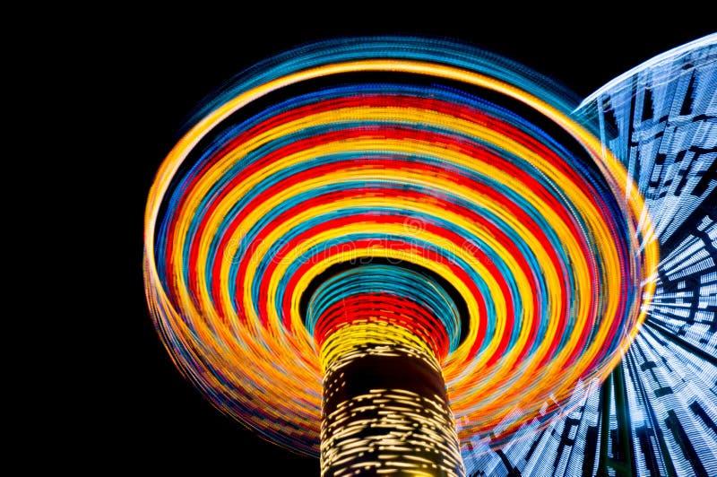 Carousel и ferris катят внутри парк атракционов вечером, долгая выдержка Концепция скорости стоковые фотографии rf