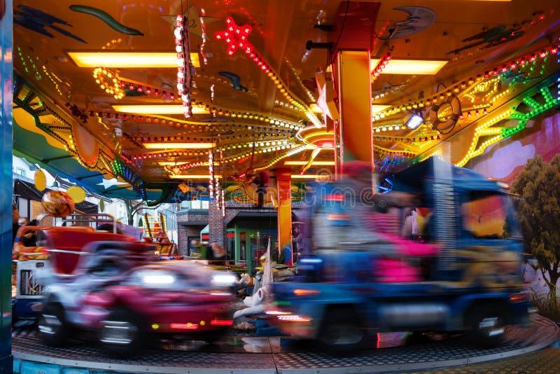 Carousel на рынке ярмарки рождества, выдержка автомобиля детей долгого времени с запачканным движением, абстрактной предпосылкой, стоковое фото rf