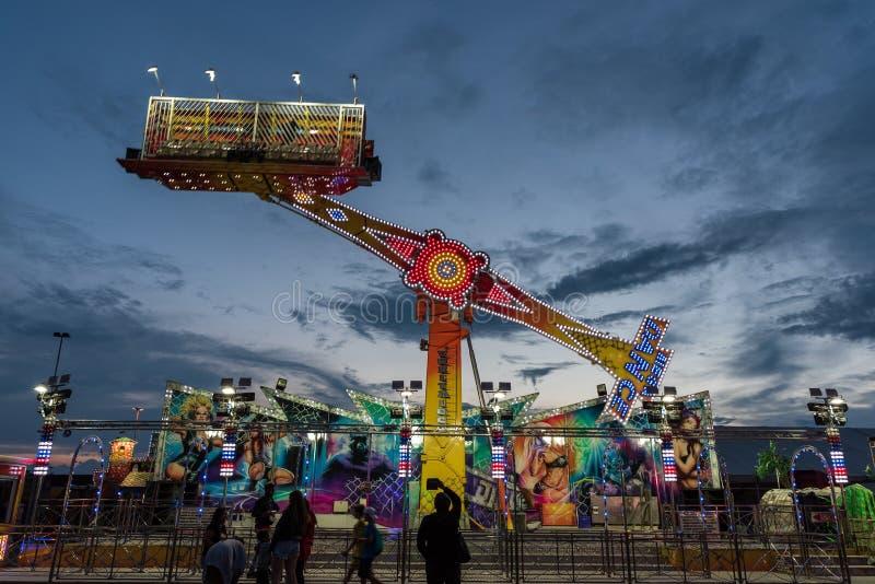 Carousel с много светов поворачивает быстро перед устоичивым spectato стоковые фото