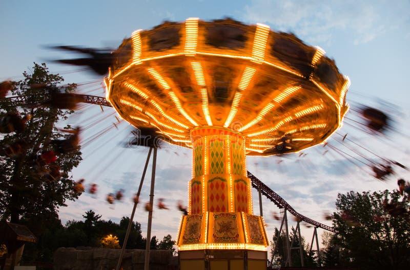 Carousel in amusement park. Motion blurred carousel ride in amusement park stock photo