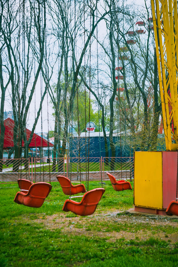 Carousel awaits visitors. Empty spring old amusement Park, chain swing carousel awaits visitors, FILTERED for retro effect stock photo
