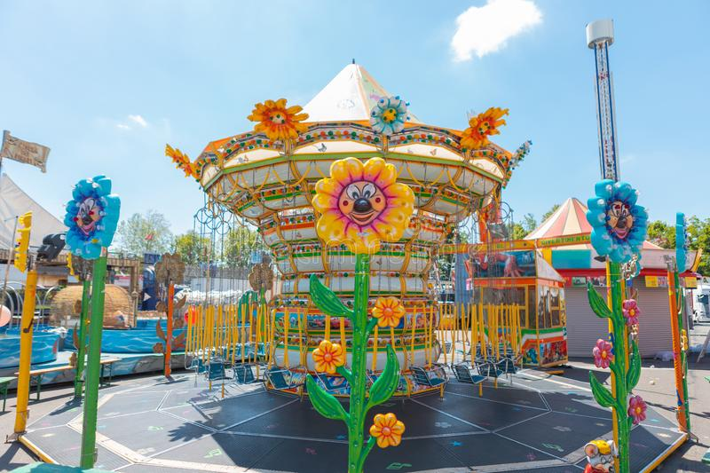 Carousel chains for children in bright colors during a fair in an Italian park flower shaped lights stock images