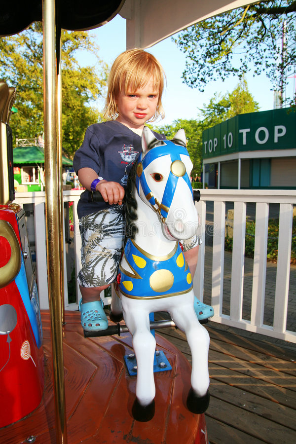 Carousel horse and child. Child on mary go round at amusement park. Kid on horse carousel ride at fair stock photos