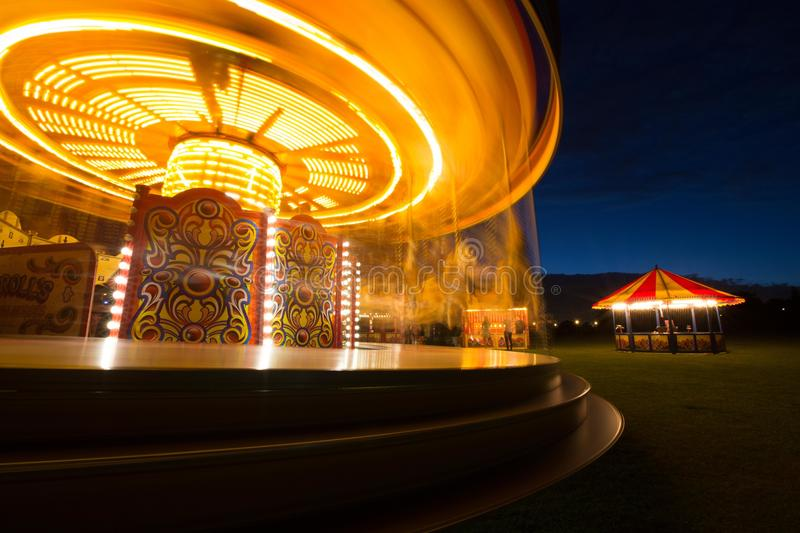 Fairground carousel at night. Carousel, merry-go-round, Tiovivo at golden hour night time. Mystical image of the spinning lights of the fun fair carousel, with a royalty free stock images