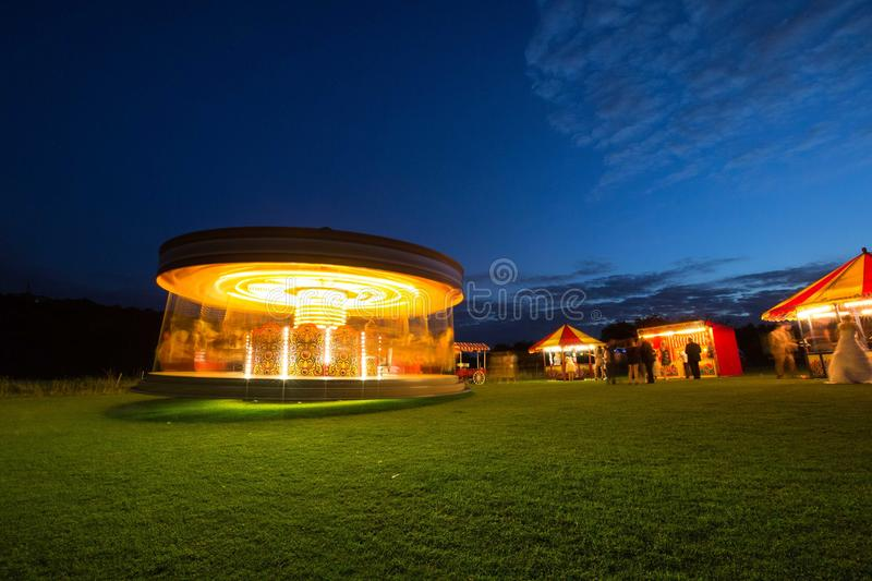 Carousel at night with funfair. Carousel, merry-go-round, Tiovivo at golden hour, outside on the green grass with blue sky and beautiful festive lights. Fun royalty free stock photos