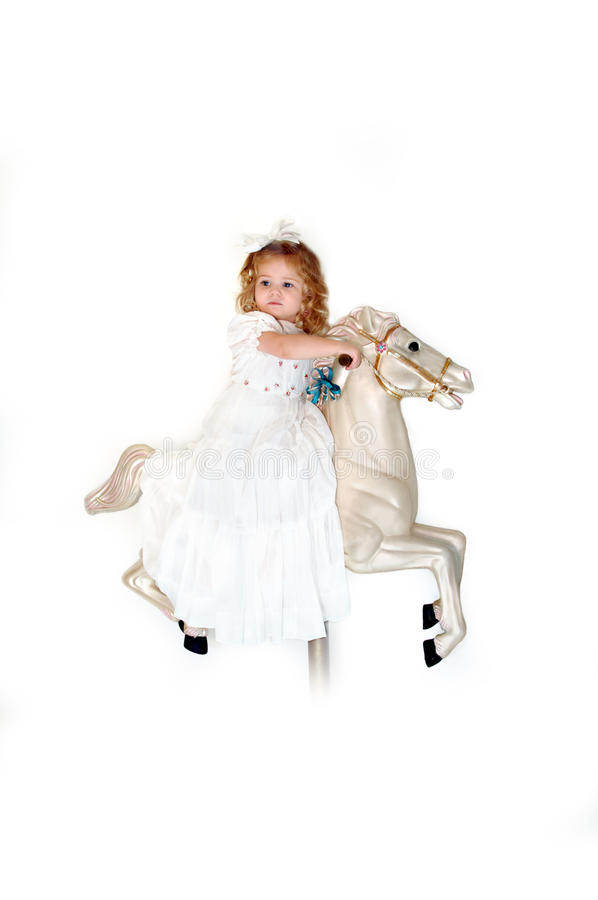 Carousel Ride. Small child rides a carousel horse in a white dress and white hairbow. She is thrilled and excited as she imagines her wild ride through the skies royalty free stock photo
