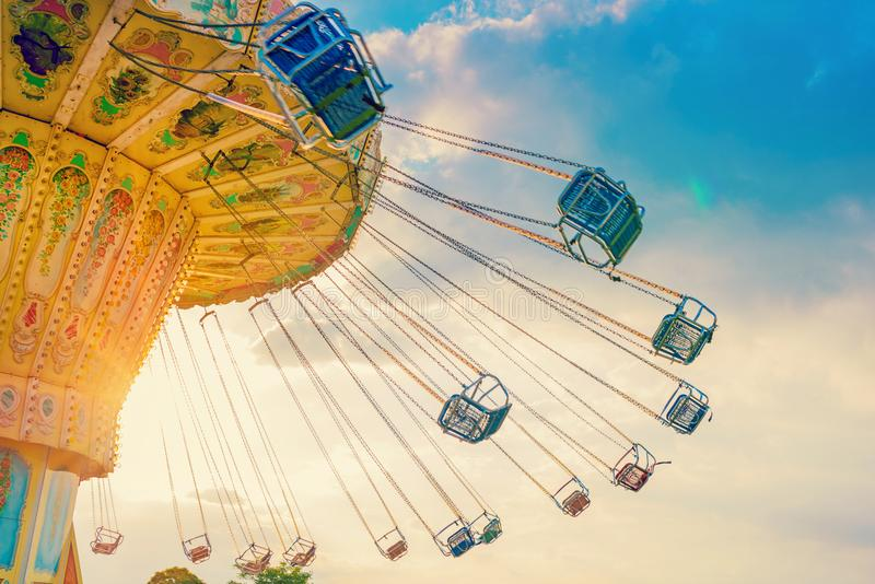 carousel ride spins fast in the air at sunset - a swinging carousel fair ride at dusk royalty free stock image