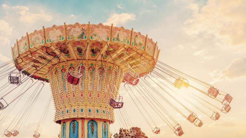 Carousel ride spins fast in the air at sunset - vintage filter e. Ffects - a swinging carousel fair ride at dusk stock images