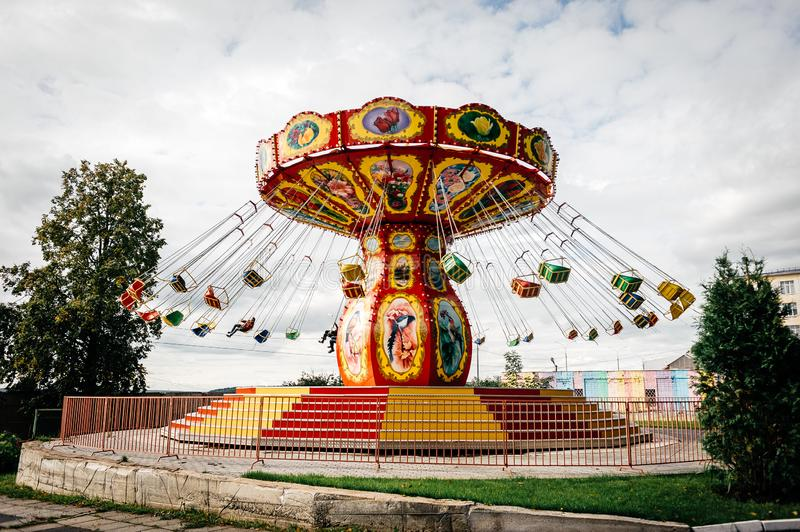Carousel whirlwind in the park against a cloudy sky stock photography