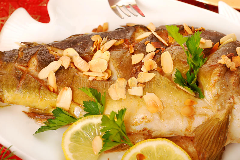 Carp baked with almonds on christmas table royalty free stock photos