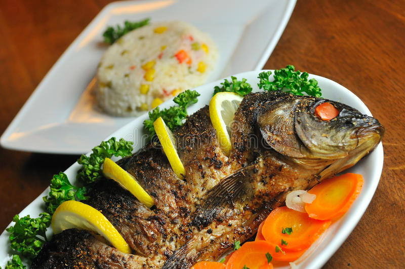 Carp baked with vegetables stock images