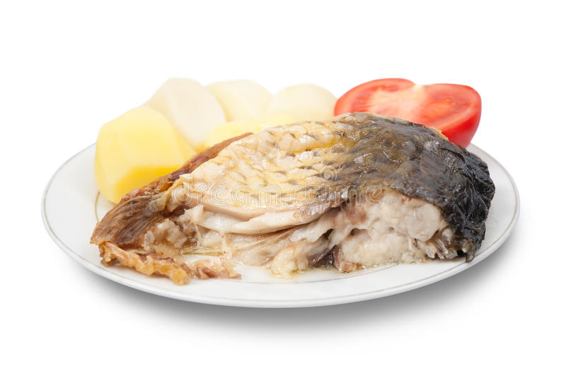 Carp fish with potatoes. Grilled carp fish with potatoes and tomato on the white plate stock image