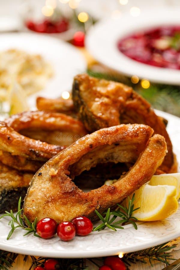 Carpa de la Navidad, rebanadas de pescados fritas de la carpa en una placa blanca, cierre para arriba imagen de archivo libre de regalías