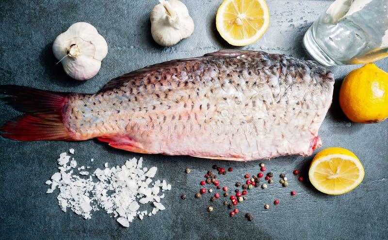 Carpa deliciosa dos peixes frescos no fundo escuro para o alimento saudável, dieta ou conceito do vintage do cozimento, foco sele fotografia de stock