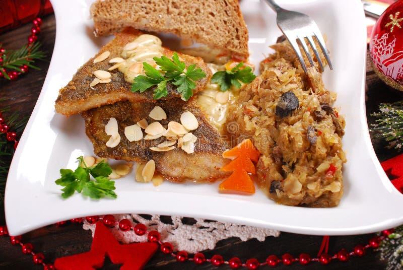 Carpa frita con las almendras y la chucrut para la Nochebuena fotos de archivo