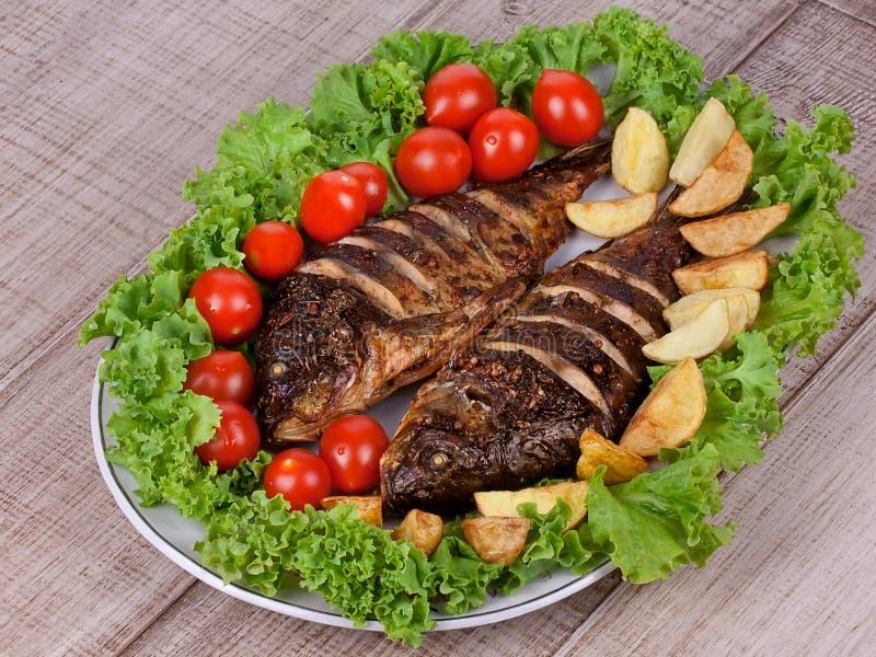 A carpa grelhada dos peixes serviu com batatas, tomates cereja e salada fotografia de stock