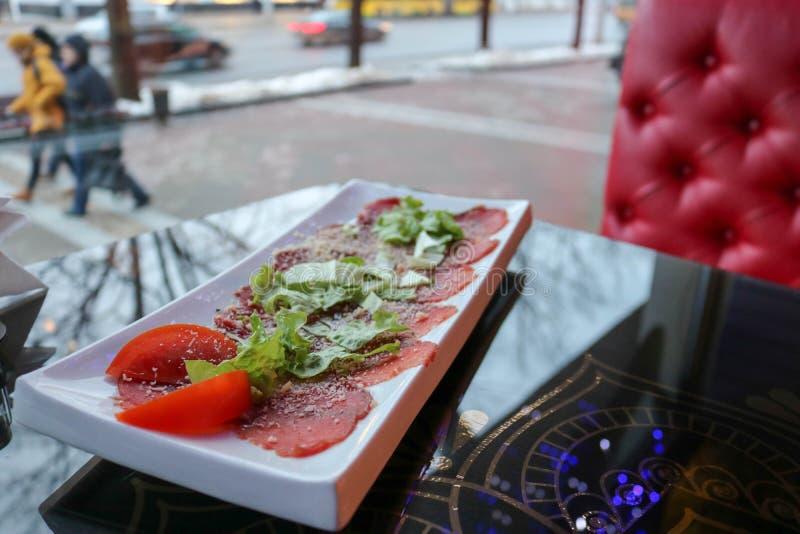 Carpaccio av rött nötkött och griskött med tomater som strilas med ost och gräsplaner på en vit rektangulär platta på en tabell i fotografering för bildbyråer