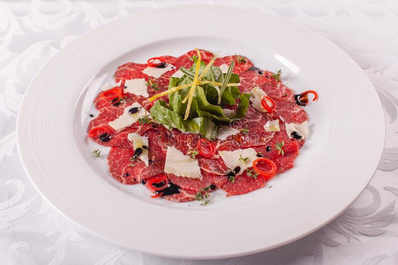 Carpaccio , beef steak salad. Summer launch, healthy eating concept. white plate with sauce. salad served in italian. Carpaccio , beef steak salad. Summer launch royalty free stock photos