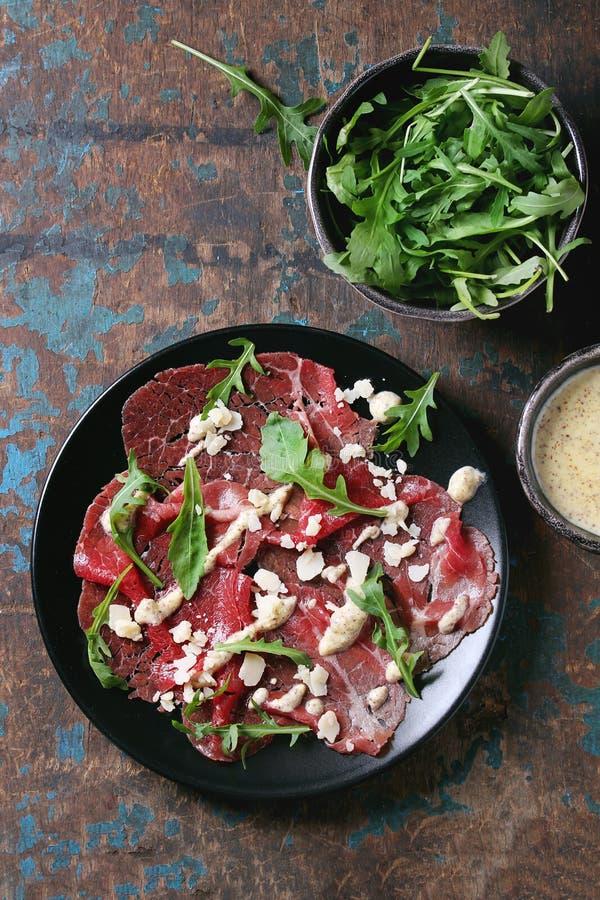 Carpaccio da carne com rúcula e molho fotos de stock
