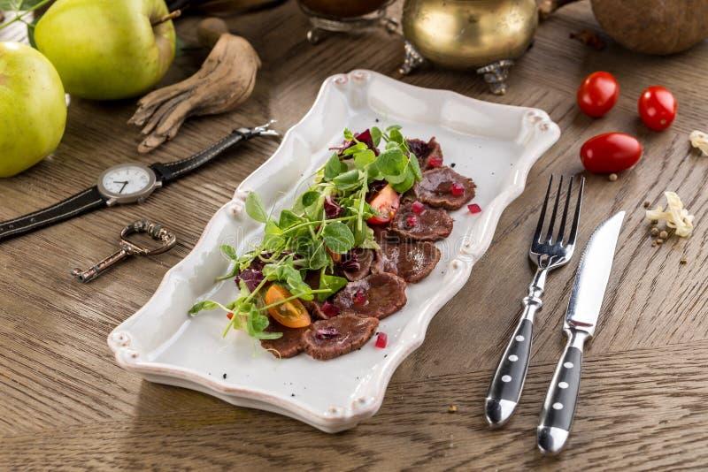 Carpaccio della carne con insalata ed i pomodori sulla tavola di legno immagine stock libera da diritti