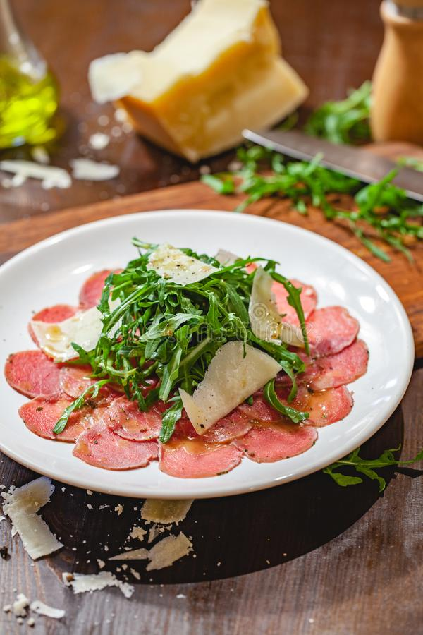 Carpaccio della carne con la rucola ed il parmigiano sul piatto bianco immagine stock