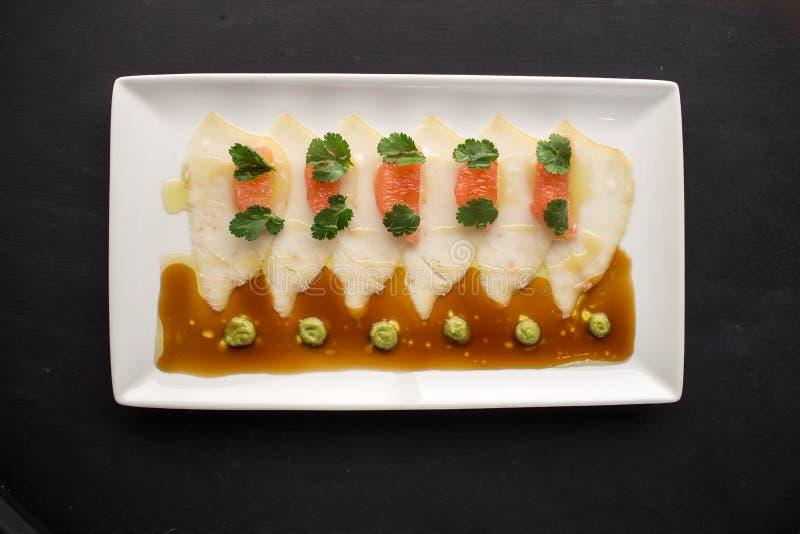 Carpaccio dos peixes brancos com toranja, molho de soja e wasabi no fundo preto fotos de stock