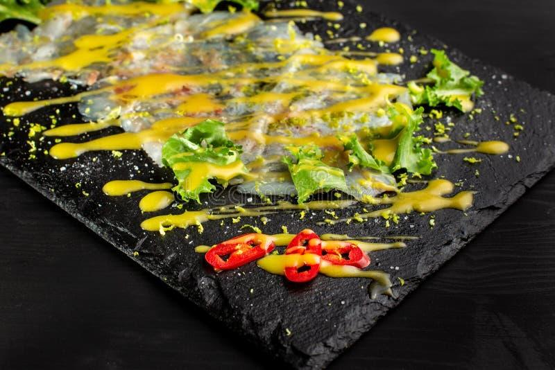 Carpaccio fish food. White fish carpaccio, poured with sauce. royalty free stock image