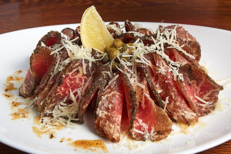 Carpaccio, gerookt vlees met geraspte kaas, citroen, kappertjes, met saus stock afbeeldingen