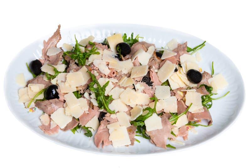 Carpaccio sałatka Średnia pieczona wołowina z parmesan, oliwkami i świeżymi ziele na talerzu odizolowywającym na białym tle, Poję fotografia royalty free