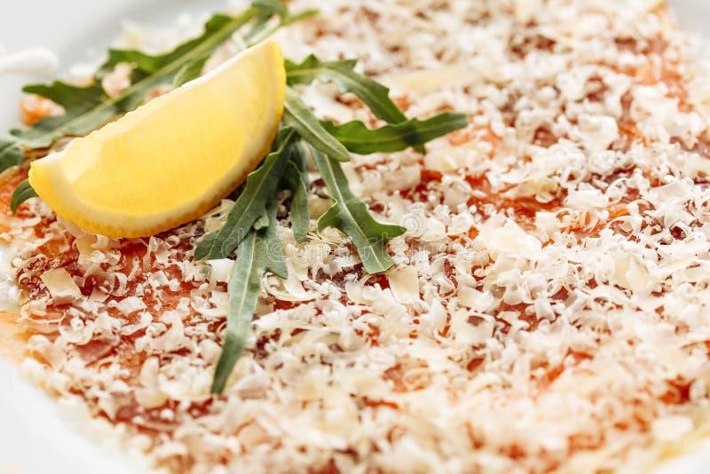 Carpaccio von den Lachsen bedeckt mit Parmesankäse, Arugula- und Zitronenscheibe Nahe Makroansicht stockfoto