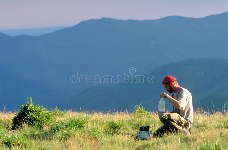 Carpathian hiker. Hiker in the Carpathians cooking dinner, Penteleu Mountains, Romania stock image