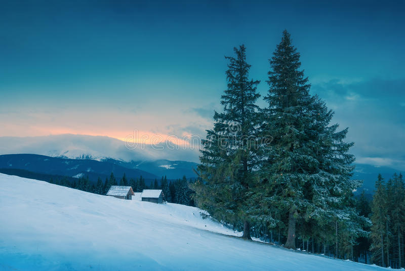 Carpathian winter snowy mountains with rustic wooden houses on a stock photo