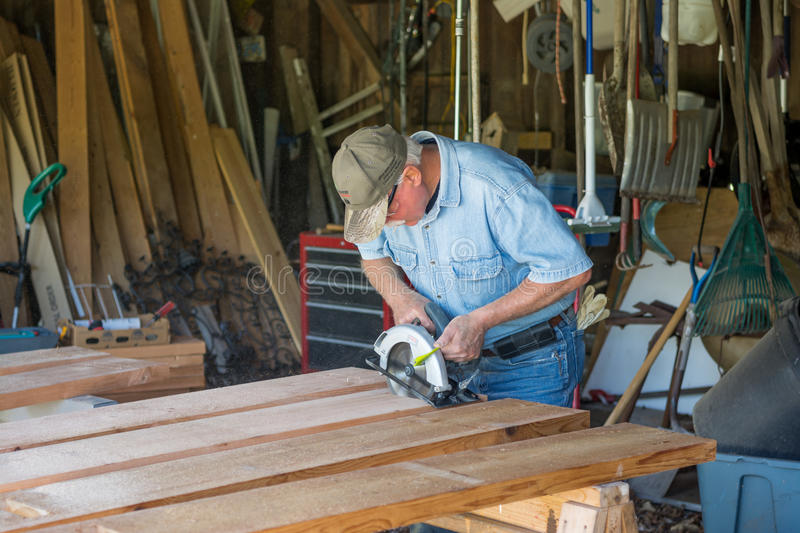 CarpCarpenter sawing 2x8 planks for garden boxes for veterans. Handy Man sawing 2x8 planks of wood for garden boxes to help veterans with PSTD and or medical royalty free stock photos