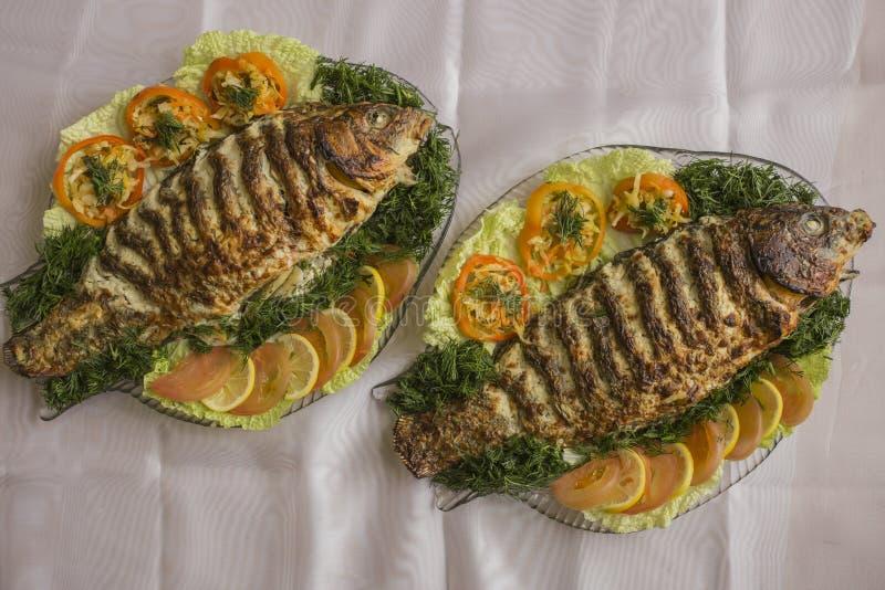 Carpe bourrée, décorée des légumes Plat de poisson images libres de droits