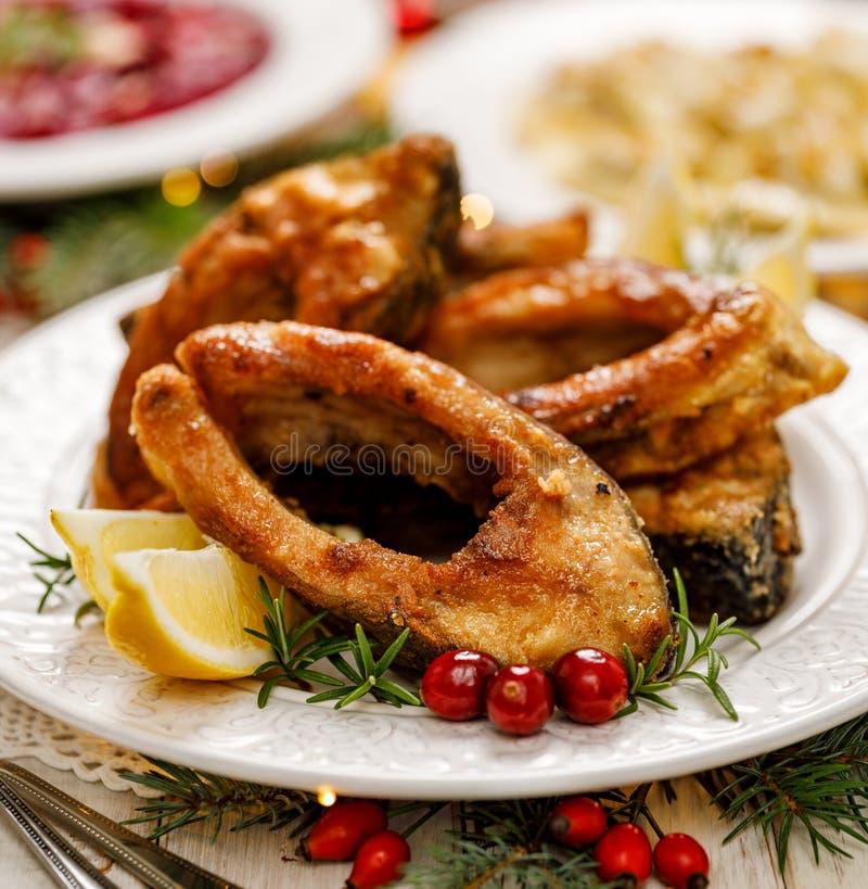 Carpe de Noël, tranches de poissons frites de carpe d'un plat blanc, fin  images libres de droits