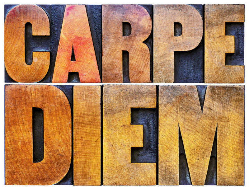 Carpe Diem in letterpress wood type. Carpe Diem - enjoy life before it is too late, existential cautionary Latin phrase by Horace - isolated text in vintage royalty free stock photos