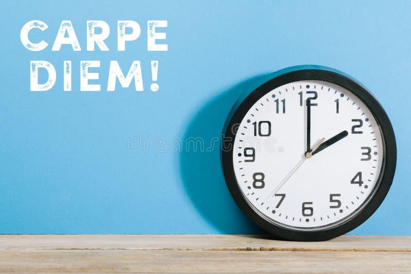Carpe diem palabras en fondo coloreado azul con el reloj imagen de archivo