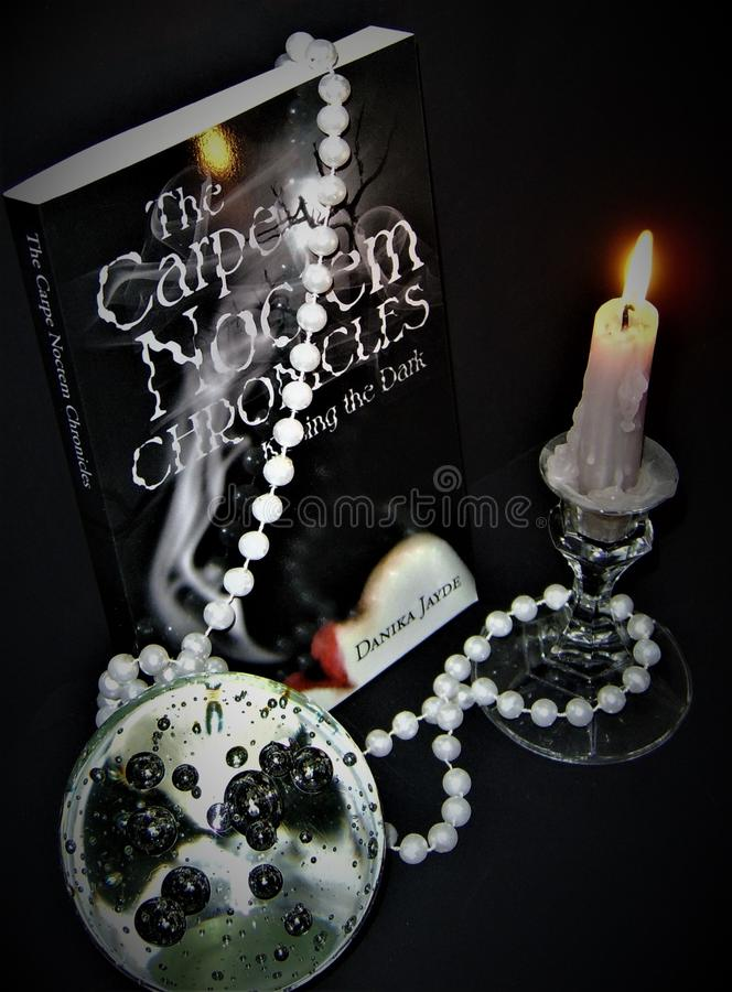 The Carpe Noctem Chronicles Book 1: Kissing The Dark. Next to a burning candle with a pearl necklace dangling from it and glass ball nearby royalty free stock photography