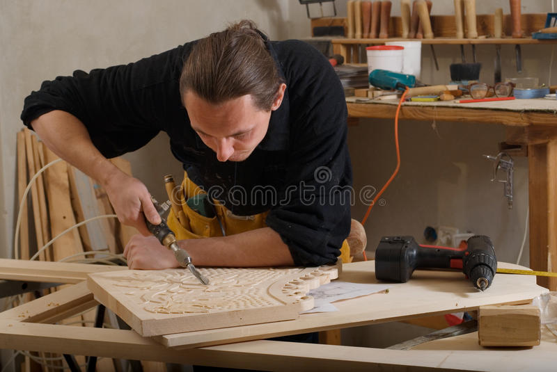 Carpenter. Young carpenter working with pneumatic chisel in his workshop royalty free stock photos