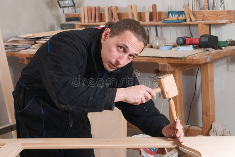 Carpenter. Young carpenter working in his workshop with chisel and wooden hammer stock images