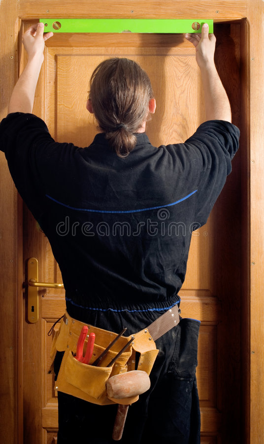 Carpenter. Checking the level on the doors stock images