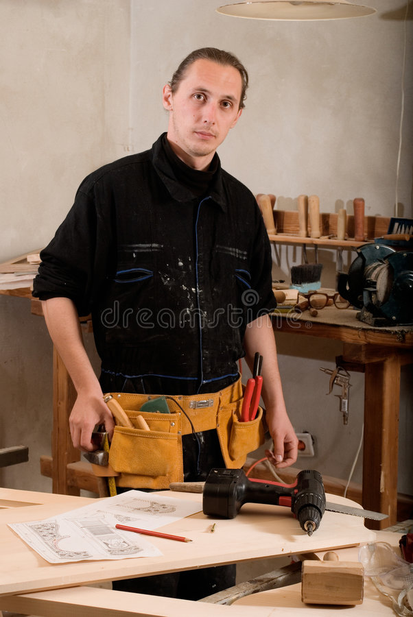 Carpenter. Young carpenter with tools belt in his workshop stock photography
