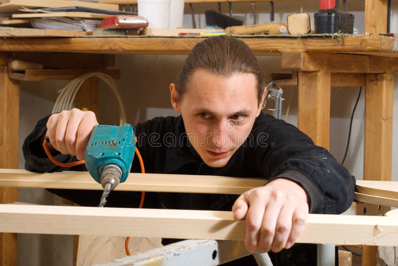 Carpenter. Young carpenter bore a hole in wooden door in his workshop stock photo