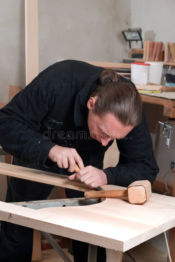 Carpenter. Young carpenter working in his workshop with hand tools royalty free stock images