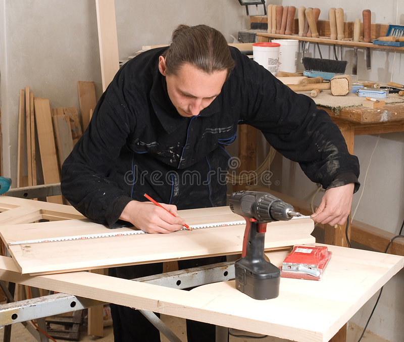 Carpenter. Young carpenter making measure with meter in workshop royalty free stock photography