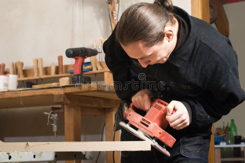 Carpenter. Young carpenter working in his workshop with polishing mashnie stock photography