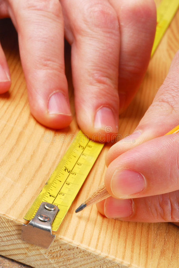 Carpenter. Is measuring wood, very close stock photography