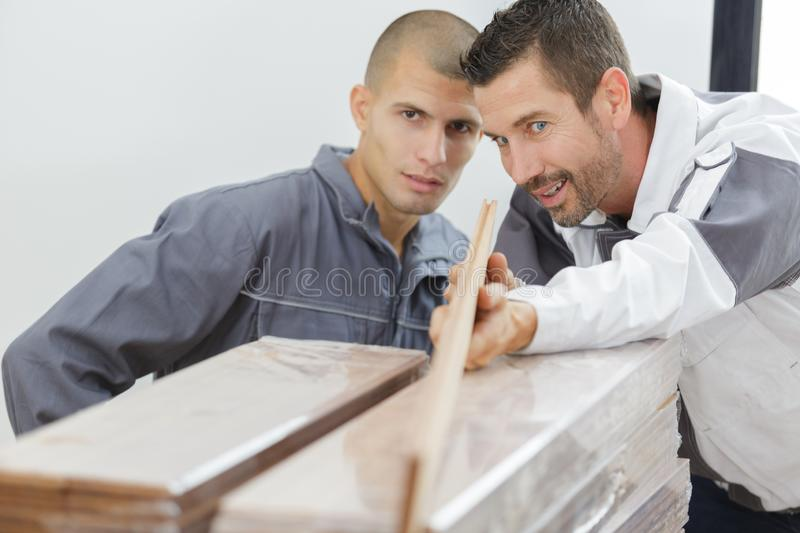 Carpenter with apprentice checking wood straight. Carpenter with apprentice checking wood is straight royalty free stock photos