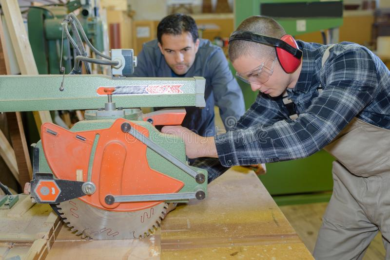 Carpenter with apprentice in training period royalty free stock images