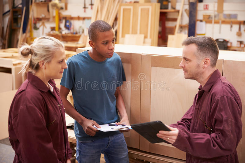 Carpenter With Apprentices Building Furniture In Workshop stock photos